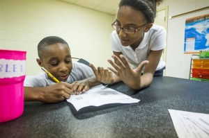 American Way Middle School eighth-grader Mya Woods, right, helps Knight Road Elementary third-grader Cordell Bailey with a math assignment at the MAM Academic Program. (Daily News/Andrew J. Breig)