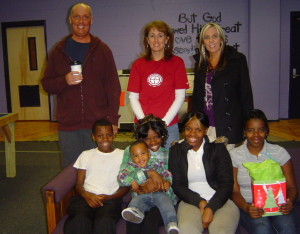 Tracey Bravos with Ed Mayo, MAM neighborhood director, and the served family for the first year in 2011